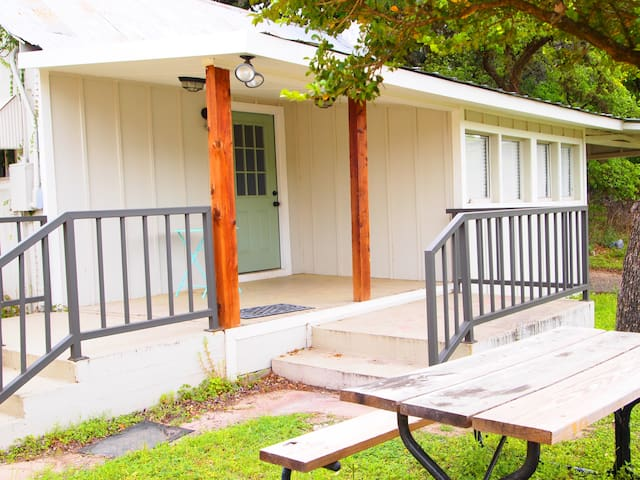 Limited amenities but kitchenware is provided. Guests must bring their own linen and towels.  Charcoal BBQ pit is at the left of this cabin.