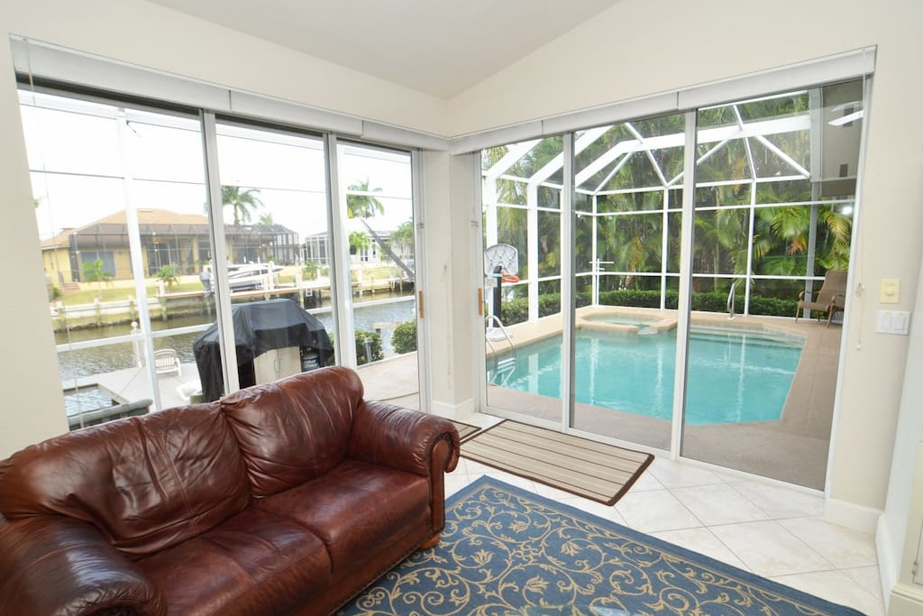 Living room enclosed by glass doors that access the pool area