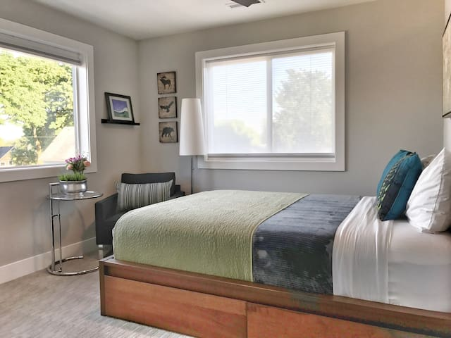 This room features a queen sized bed with memory foam mattress, two large windows with room darkening shades, side chair and table, and a ceiling fan.