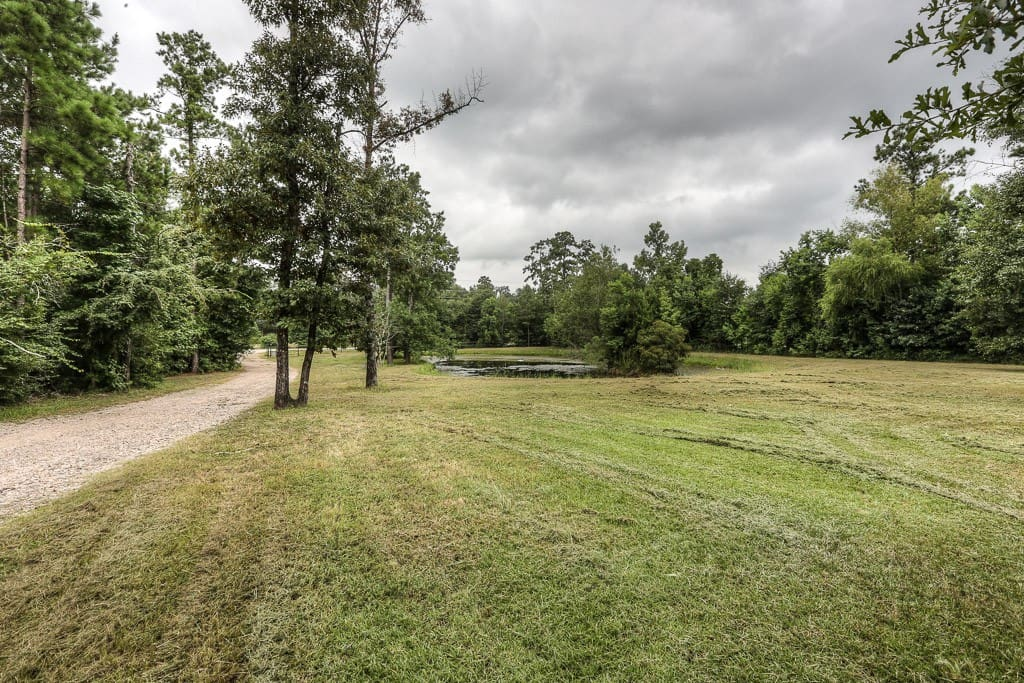 Gated entry leads you down a winding dirt road past a private lake to hideaway destination!