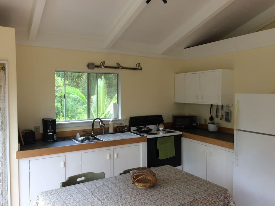 Closer view on kitchen, pots and pans, toaster, coffee maker, and microwave. Great garden view!