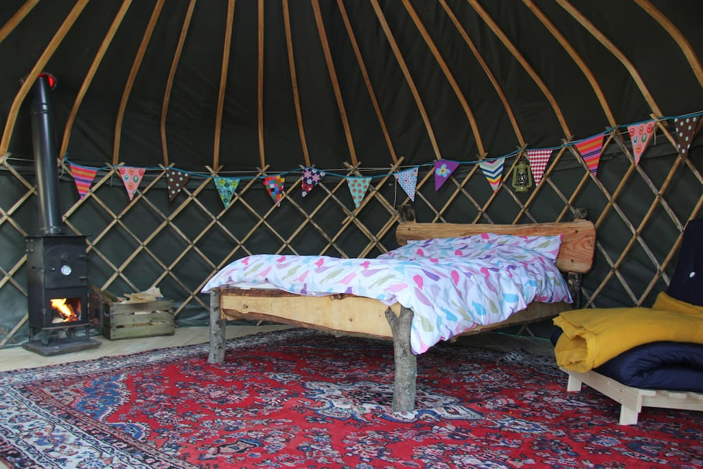 Cosy inside of Yurt with wood burner and home made bed
