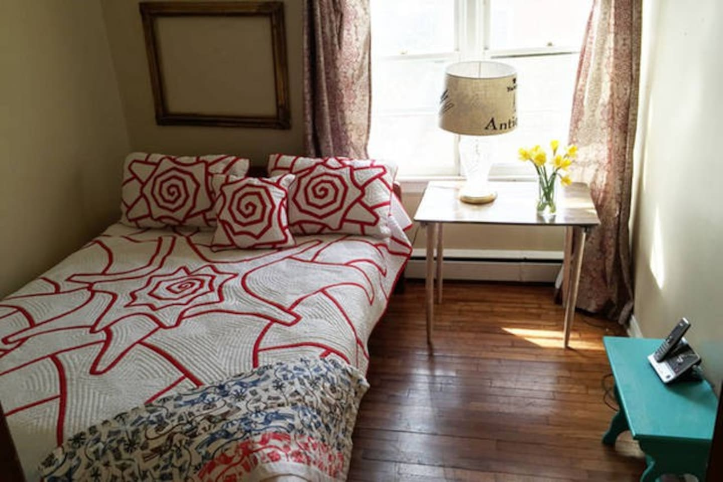 Queen size bed with Ralph Lauren linens. Two windows, wood floors . solid wood bed frame is a little low at 19 inches high.