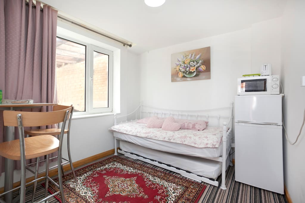 Good size Sitting area with comfortable bed, fridge-freezer, Microwave and table-chairs.