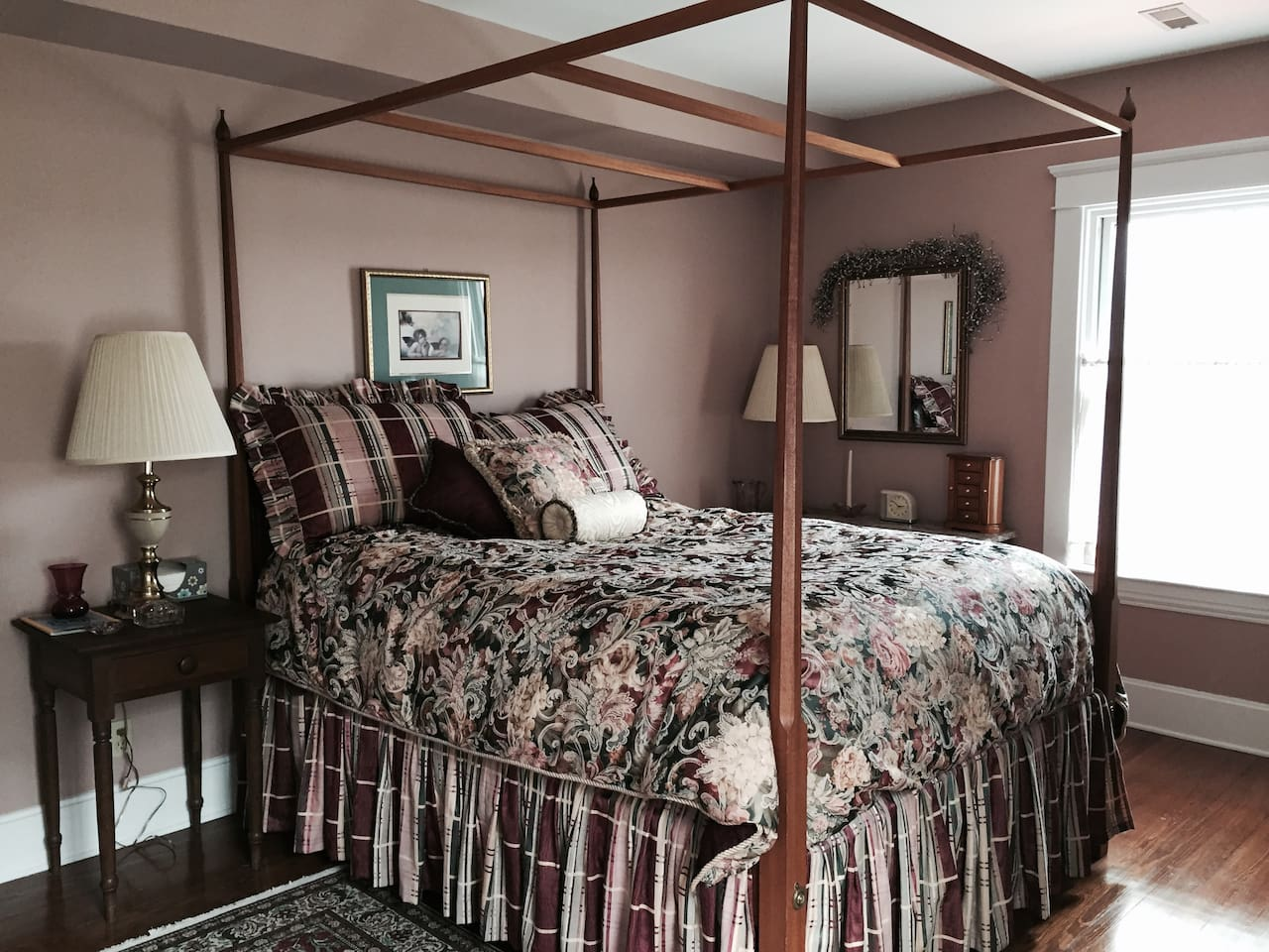 Queen-size poster bed with custom-made bedding is large and at front of the three story house.