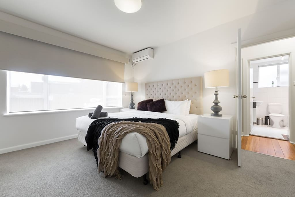 Spacious king bedroom with large bedside tables and lamps, plenty of storage space, robes with huge mirrored doors, double glazing, air-con, daylight and block-out blinds, in this StayCentral 2 bedroom serviced Brunswick apartment