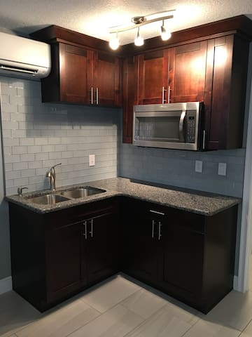Kitchenette with microwave, double stainless steel sink, and granite counter top.