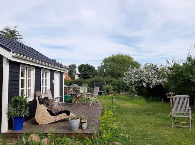 Hyggelig hytte i frodig have, tæt på vandet
