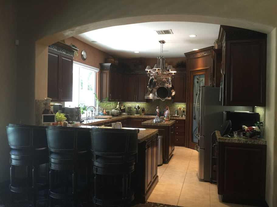 Kitchen with counter seating, new refrigerator and espresso machine