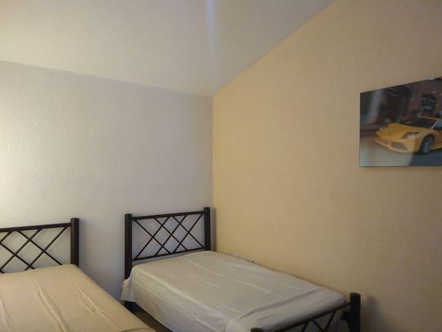 Recamara 2 camas individuales con almohadas y closet