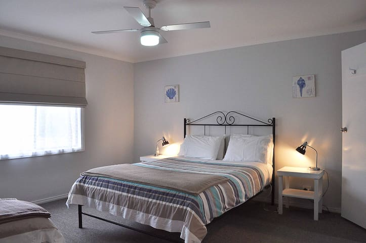 Main bedroom with queen size bed and en-suite and ceiling fan.