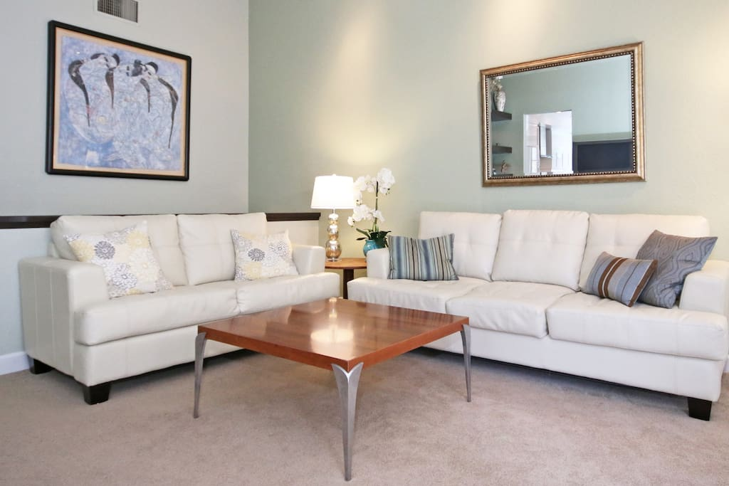 Spacious living room is furnished with a leather sofa sleeper, love seat and entertainment center.