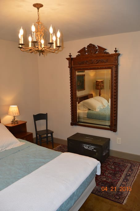 Queen size bed, fabulous antique walnut mirror, old military trunk.