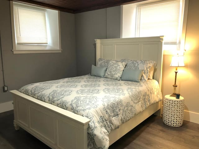 Bedroom #1 has 3 bright windows with blinds for privacy and darkness. Soft sheets, fluffy pillows and a queen bed for a relaxing sleep. There's even an antique chair for your comfort.