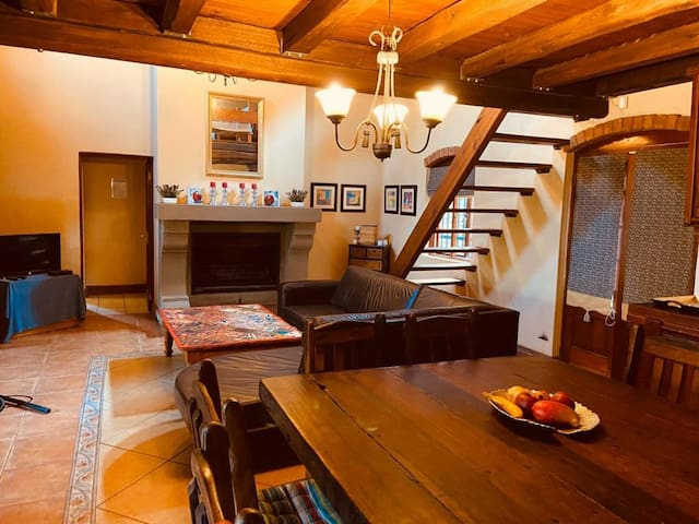 Openplan living and diningroom with fireplace. Stairs going up to loft area.
