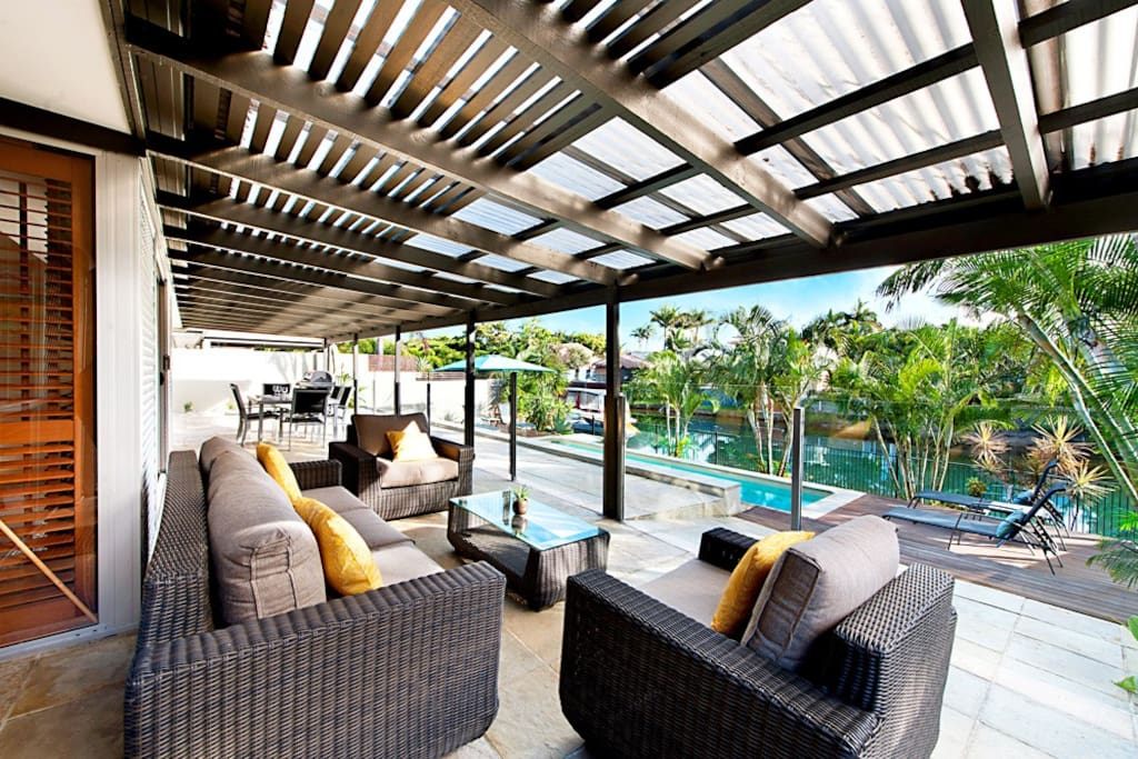 Fully fenced pool with lounge and outdoor dining area outside of pool for evening entertaining with children's safety in mind