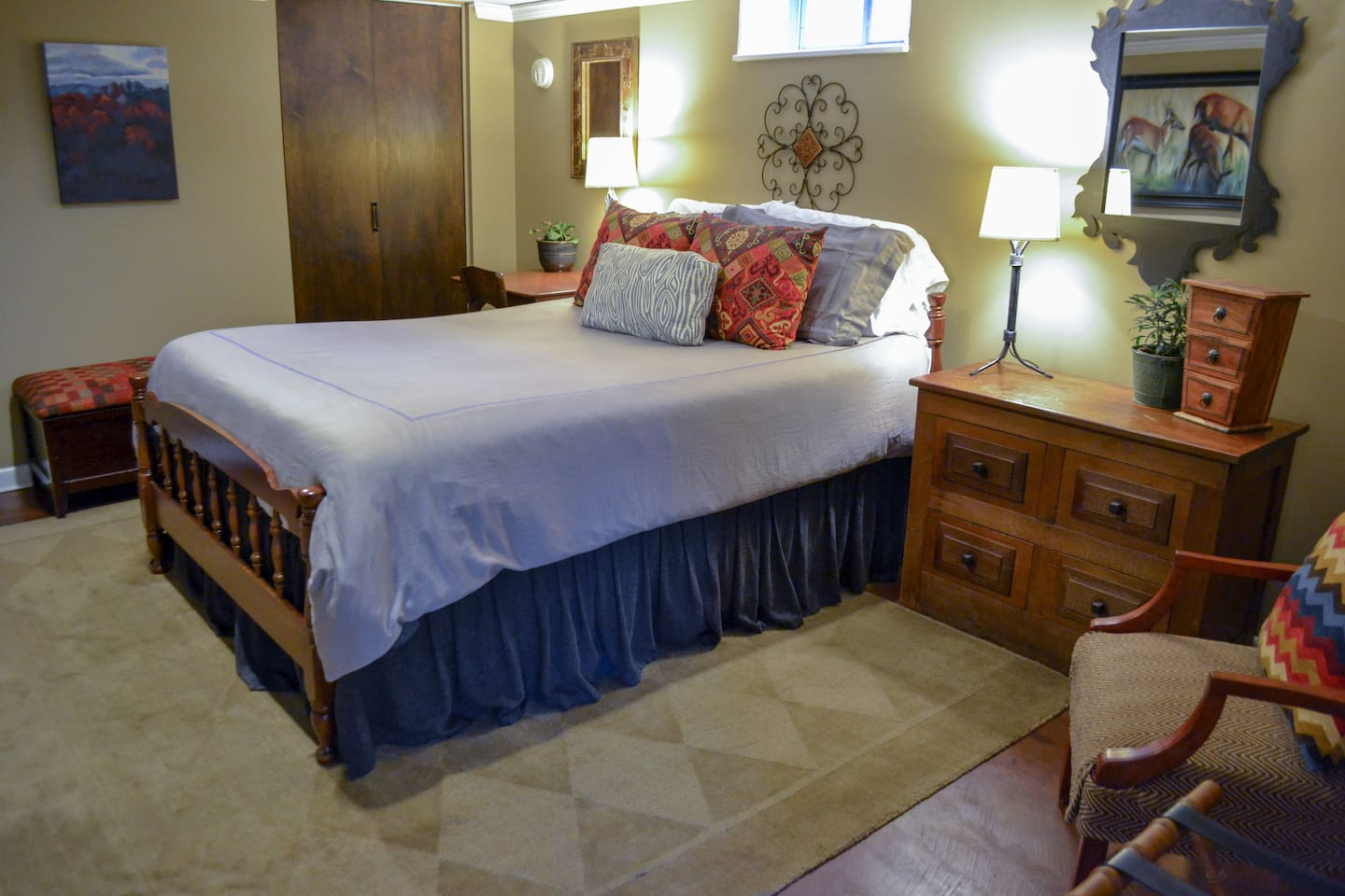 Bedroom with queen-sized bed, empty dresser & closet for your use, as well as seating.