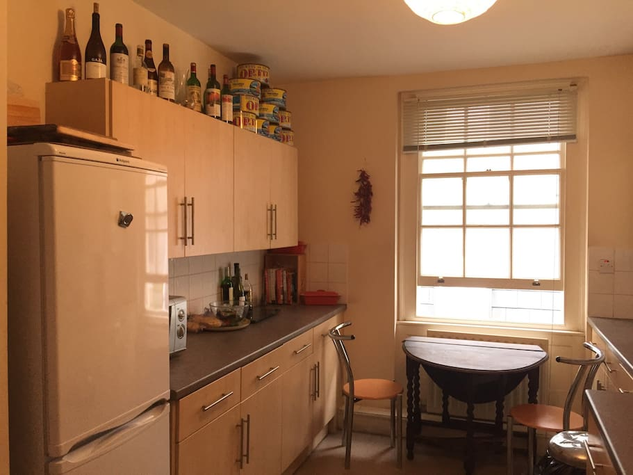 Bright side of kitchen with table and chairs.