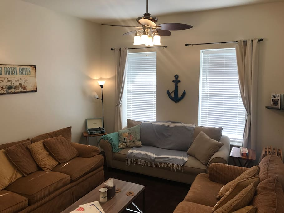 "Living room is large enough to seat everyone, complete with high ceilings, 55"" HD TV, Roku w/Netflix & Sling, BlueRay, Chromecast, vinyl record & bluetooth player, lamp and queen pull out sofa bed.  There are also 6 wooden foldout TV tables for dinners or party hosting."