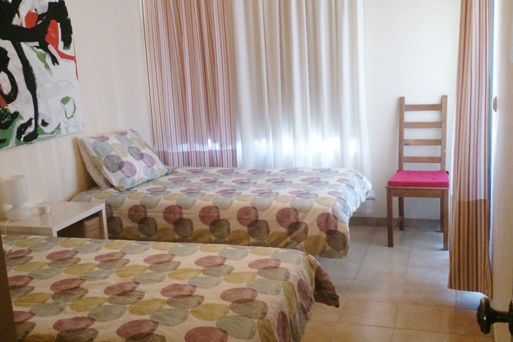 bedroom with two single beds. from here you can access the balcony. It has a large wardrobe.