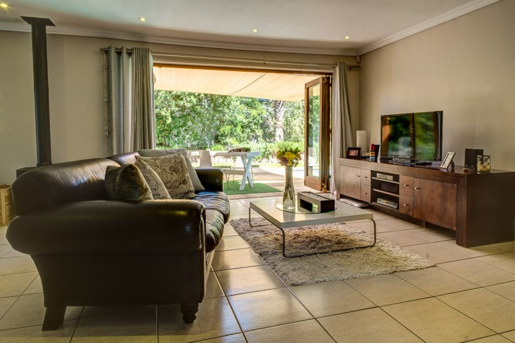 TV Room opening onto shaded braai and pool area