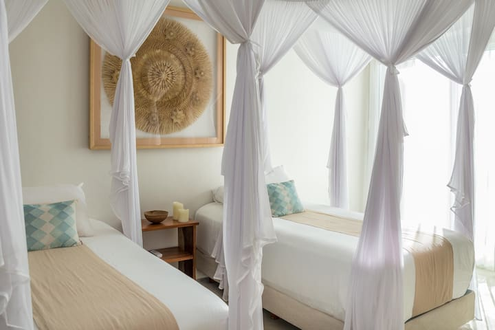 Twin bedroom with local framed weaving details and mosquito nets with access to the oceanfront terrace. There is an outdoor shower on the terrace so you can wash the sand off before you take a siesta.