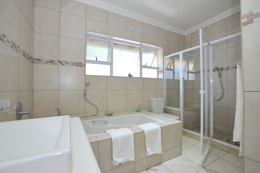 The Court Yard - large bathroom with walk in shower and seat