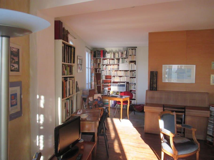Un piano, une bibliothèque  et, au fond une chambre non fermée