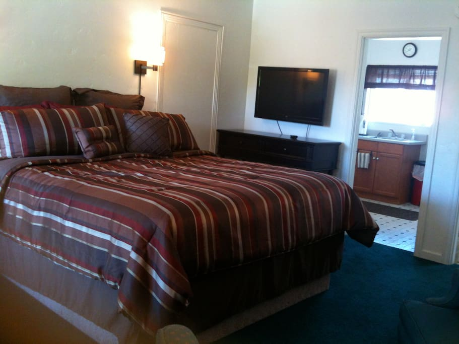 King bed with side reading lamps, flat screen TV, and WIFI access