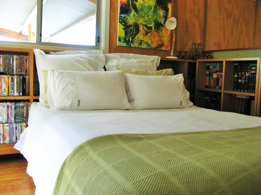 Main bed is flanked by a library of books, DVDs & CDs - mixed genres & for all ages.
