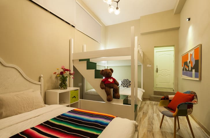 这间有有趣的梦想复式套房,有三张1.8米的大床,可以住6个人哦。我超喜欢坐在绿色楼梯上的大熊