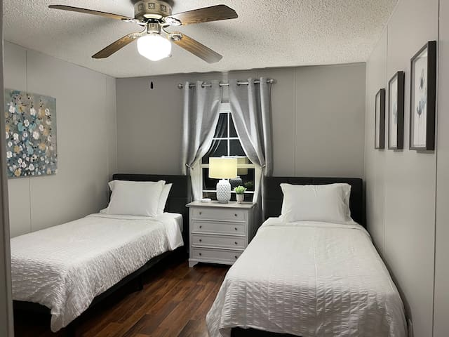 Bedroom 3 contains two twin beds. Nightstand/dresser has a lamp and charging station with ports for AC adapters and USB.