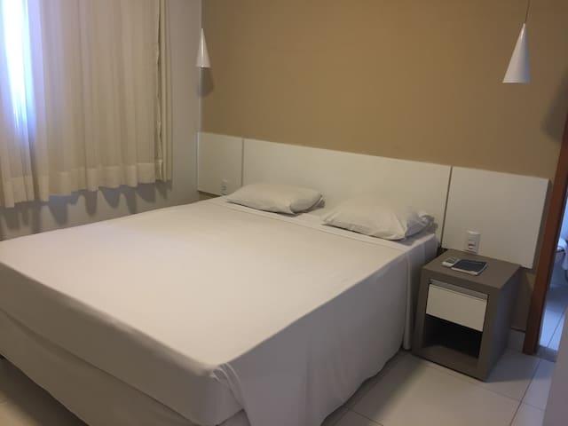 Suíte casal com cama larga, ar condicionado, armário, tv smart e banheiro
