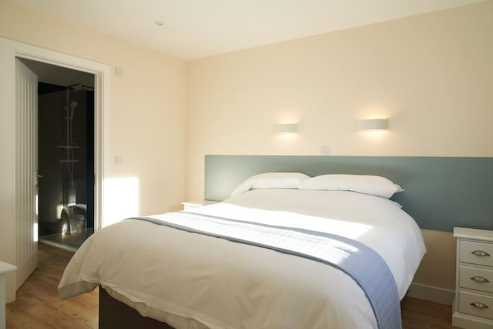 King/ Twin en suite bedroom (Zip and link) with large walk in  shower. This room also has a patio door leading onto a sunny patio and private hot tub.