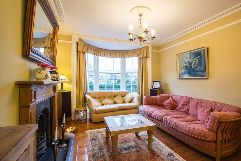 Sitting room with coal effect gas fire and views across the square (gold sofa now replaced with 2 armchairs).