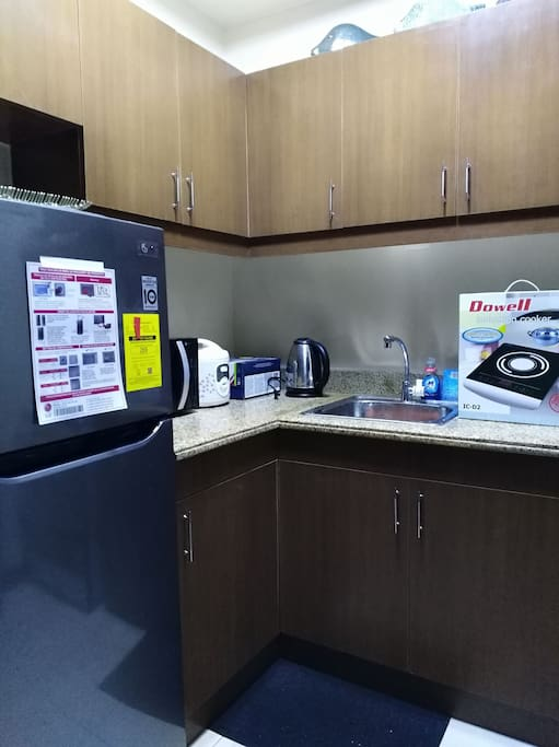 Kitchen is equipped with dining set, cooking wares, ref, kettle microwave, rice cooker and induction cooker