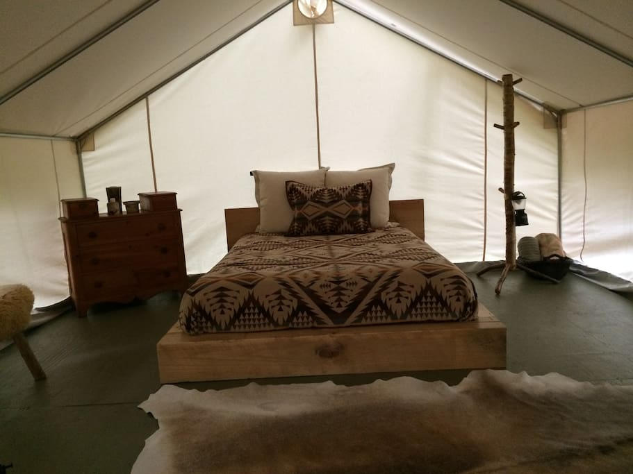 The cozy interior of our tent with Queen bed & wood stove.
