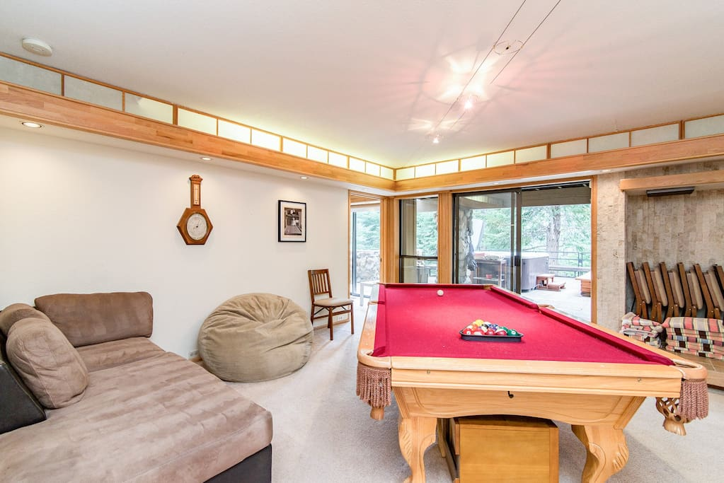 A pool table and additional seating in the game room.