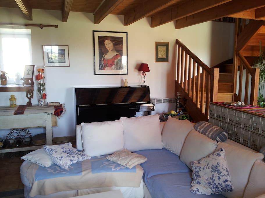 Le salon avec piano droit et grand canapé