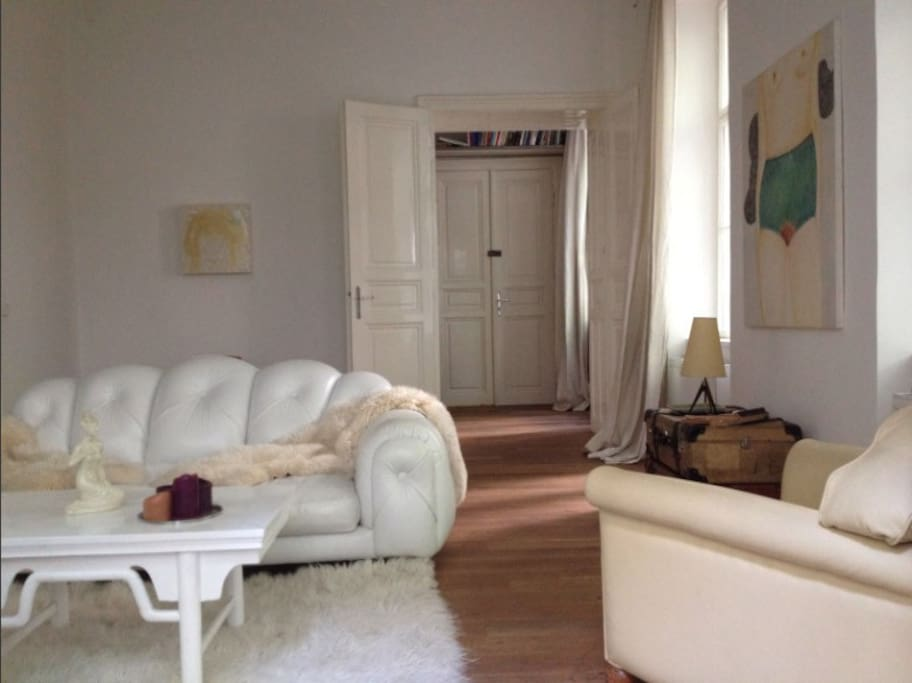 Lounge area with white leather sofa, entrance door.