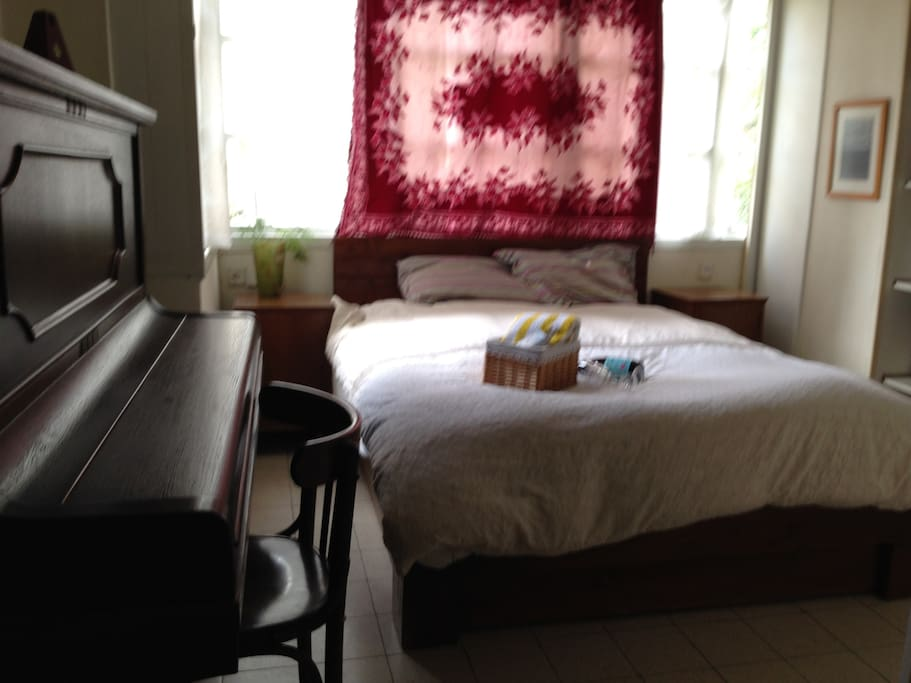 This is your private room.The double real bad is big and comfortable. Have your quiet place .  Aircondition in your  room and a lot of place for your belongings. Yes you can play the Piano!