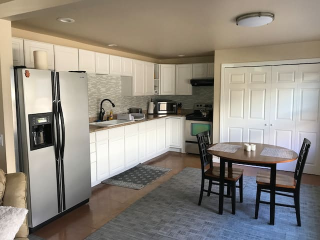 Large, clean kitchen with washer & dryer behind sliding doors.