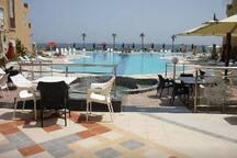 Vue piscine et mer depuis le café de la résidence