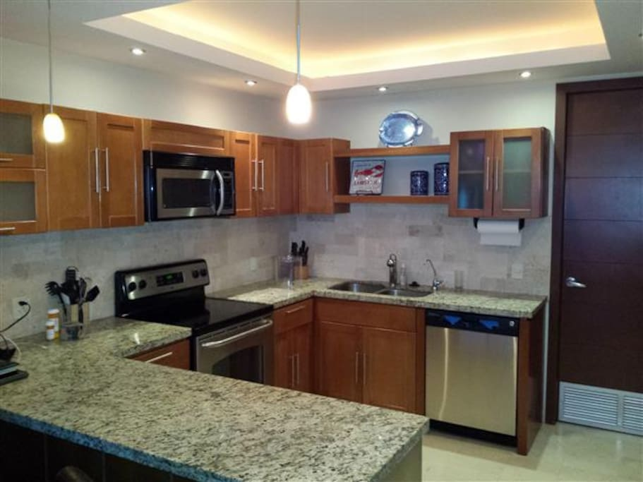 Modern kitchen with 4 burner stove, large oven, microwave, dishwasher and side-by-side refrigerator and freezer.