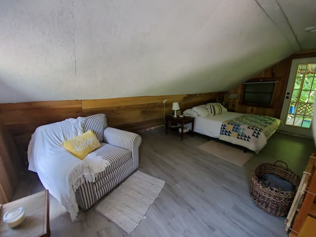 Upstairs loft with a queen bed and a big comfy chair