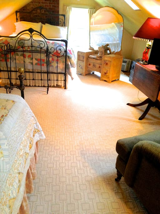 Second bedroom of suite with queen and double beds , small refrigerator