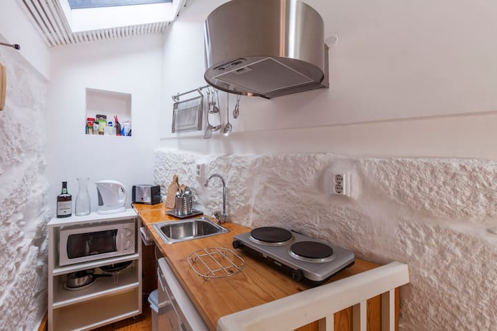 The kitchen is equipped with microwave, exhaust fume, stove, coffee maker, dishes and fridge.