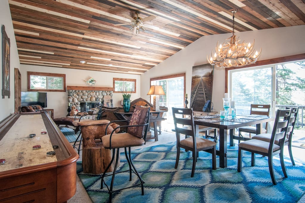 Great room has new 8 person custom dining table, 14 foot shuffle board, tv, fireplace, views of lake!
