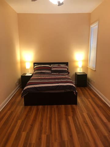 Main Master Bedroom with full size platform bed with built in drawers, new floors, walk-in closet in room, bedside tables lamps and remote controlled ceiling fan.