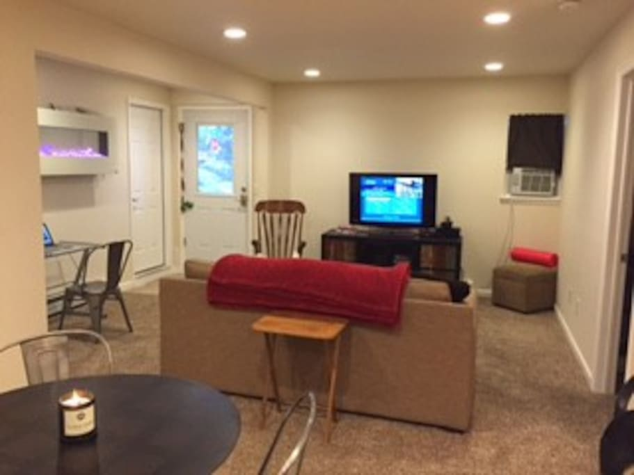 Living room with electric fireplace, TV, and entrance to apartment.